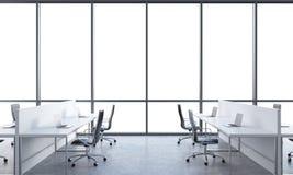 Lugares de trabajo en una oficina moderna brillante del espacio abierto Tablas blancas equipadas de los ordenadores portátiles mo Fotografía de archivo