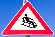 Luge warning sign. In germany - in front of blue sky Royalty Free Stock Photography
