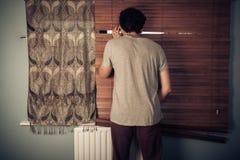 Lugender Tom, der durch Vorhänge schaut Stockbilder
