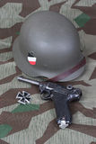 Luger P08 Parabellum handgun, helm and medal Iron Cross on camouflaged background Stock Photography
