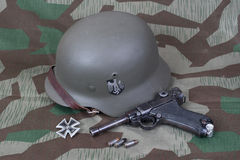 Parabellum handgun, helm and medal Iron Cross on camouflaged background Stock Image