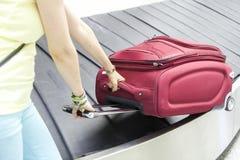 Luggage in airport conveyor belt. Passanger taking her luggage in airport conveyor belt royalty free stock photo