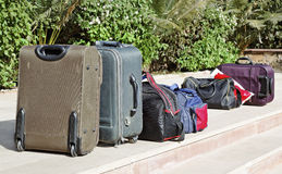 Luggage bags packed check out. Row of packed luggage in the sunshine after check out Royalty Free Stock Photo