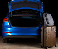 Luggage bags stand next to open car trunk. Luggage bags stand next to open car empty trunk isolated on black background Stock Images