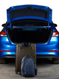 Luggage bags stand next to open car trunk. Isolated on white background Royalty Free Stock Photos
