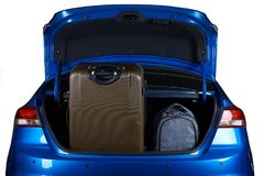 Luggage in blue modern sedan car trunk. Closeup isolated on white background Royalty Free Stock Photo