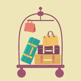 Luggage cart with suitcases and bags. On a beige background Royalty Free Stock Photography