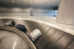 Luggage claim carousel with three bags at airport Stock Photo