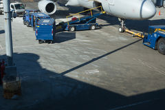 Luggage on conveyor belt by airplane cargo hold Stock Photo