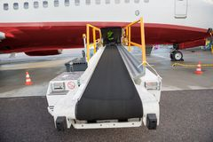 Conveyor Truck Attached To Airplane On Airport Runway Royalty Free Stock Photos