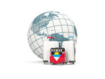 Luggage with flag of antigua and barbuda. Three bags in front of. Globe. 3D illustration Stock Photos