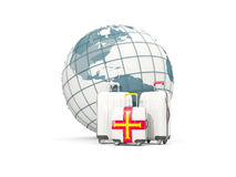 Luggage with flag of guernsey. Three bags in front of globe Royalty Free Stock Images