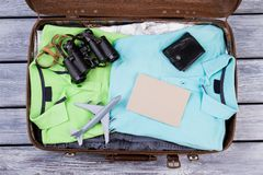 Luggage full of clothes, top view. Open packed suitcase with male summer clothes and accessories Royalty Free Stock Photos