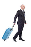 Luggage. Full length side view of young businessman with luggage walking isolated on white background Royalty Free Stock Photography