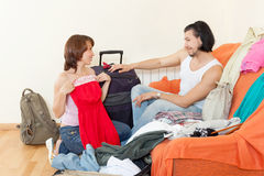 With luggage looking clothes for holiday. Couple with luggage looking clothes for holiday Stock Photography