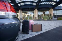 Luggage beside parked car outside hotel Stock Images