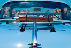 Luggage Rack. The wooden luggage rack afixed to the back boot of a classic blue car with indisctinct drowds of enthusiasts beyond just visible through the Stock Photo