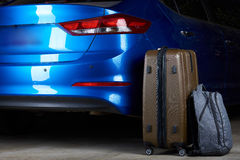 Luggage stand next to closed car trunk. Luggage stand next to closed modern blue car trunk view from back Stock Images