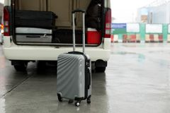 Luggage stand on the road and arrange on the van for a trip. In rainy day Stock Photos