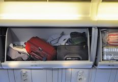 Luggage storage. Carry-on luggage in overhead storage compartment on commercial airplane Stock Image