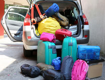 Luggage and suitcases in car for departure. Car overloaded with suitcases and duffle bag for family travel Stock Photos