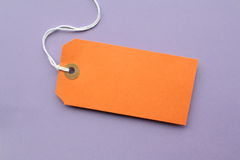 Luggage Tag. Orange paper luggage tag with copy space on a purple background Stock Photos