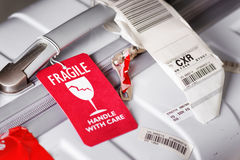 Luggage tag Fragile attached to white suitcase at airport stock image