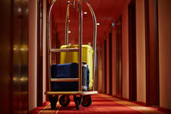Luggage of travelers. Cart of porter with suitcases in aisle of hotel Royalty Free Stock Images