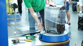 Luggage wrapping service in airport for security reason and safety protection from damage. Baggage wrapping