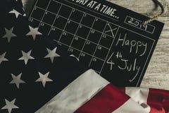4 luglio in calendario sotto la bandiera degli stati americani e tutto sulla tavola di legno, stile d'annata fotografia stock