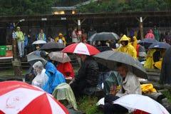11 LUGLIO 2013 - GARANA, ROMANIA Scene e la gente che si siedono o che camminano sulla via in un giorno piovoso Fotografie Stock Libere da Diritti
