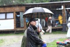 11 LUGLIO 2013 - GARANA, ROMANIA Scene e la gente che si siedono o che camminano sulla via in un giorno piovoso Immagine Stock Libera da Diritti