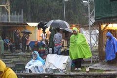 11 LUGLIO 2013 - GARANA, ROMANIA Scene e la gente che si siedono o che camminano sulla via in un giorno piovoso Immagini Stock Libere da Diritti