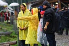 11 LUGLIO 2013 - GARANA, ROMANIA Scene e la gente che si siedono o che camminano sulla via in un giorno piovoso Immagine Stock