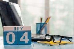 4 luglio Giorno del calendario di legno di colore di mese 4 sul fondo del posto di lavoro di affari Giovani adulti Spazio vuoto p Fotografia Stock