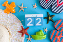 22 luglio Immagine del calendario del 22 luglio con gli accessori della spiaggia di estate e l'attrezzatura del viaggiatore su fo Fotografie Stock Libere da Diritti