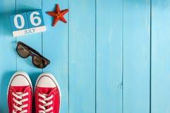 6 luglio Immagine del calendario di legno di colore del 6 luglio su fondo blu Albero nel campo Spazio vuoto per testo mondo Fotografia Stock