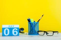6 luglio Immagine del 6 luglio, calendario su fondo giallo con gli articoli per ufficio Giovani adulti Con spazio vuoto per testo Immagini Stock