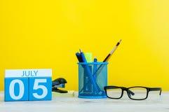 5 luglio Immagine del 5 luglio, calendario su fondo giallo con gli articoli per ufficio Giovani adulti Con spazio vuoto per testo Immagine Stock Libera da Diritti