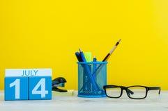 14 luglio Immagine del 14 luglio, calendario su fondo giallo con gli articoli per ufficio Giovani adulti Con spazio vuoto per tes Fotografia Stock