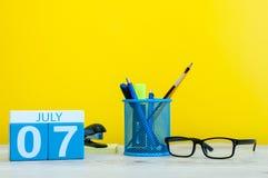 7 luglio Immagine del 7 luglio, calendario su fondo giallo con gli articoli per ufficio Giovani adulti Con spazio vuoto per testo Fotografie Stock Libere da Diritti