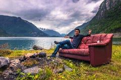 21 luglio 2015: Viaggiatore che si rilassa in uno strato rosso nel norwegia Fotografie Stock Libere da Diritti