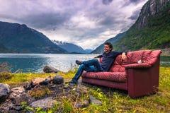 21 luglio 2015: Viaggiatore che si rilassa in uno strato rosso nel norwegia Fotografia Stock Libera da Diritti