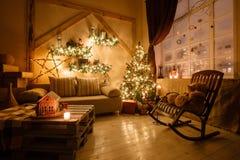Lugna bild av det inre modern hem- vardagsrum dekorerade julträdet och gåvor, soffa, tabell som täckas med filten Royaltyfri Bild