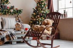Lugna bild av det inre modern hem- vardagsrum dekorerade julträdet och gåvor, soffa, tabell som täckas med filten Arkivbild
