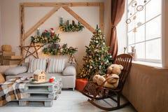 Lugna bild av det inre modern hem- vardagsrum dekorerade julträdet och gåvor, soffa, tabell som täckas med filten Royaltyfri Foto