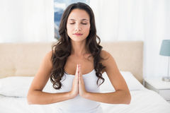Lugna brunett som gör yoga på säng Fotografering för Bildbyråer