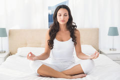 Lugna brunett som gör yoga på säng Arkivbild