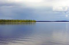 Lugna efter regnet över den nordliga sjön som omges av berg Royaltyfria Bilder
