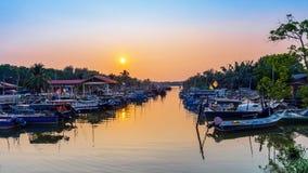 Lugna fiskeläge med fartyget under solnedgång royaltyfri bild
